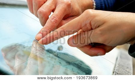 Hands forefingers pointing the places on touristic map. Focusing on landmarks and trip planning.