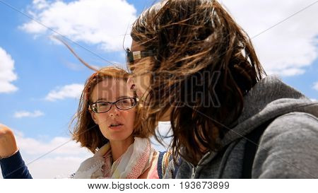 Two longhair women with hair waving and flying in the wind outdoors. Ladies talk and enjoy the cityscape on summer windy weather.