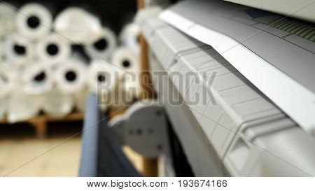 Wide format printer is printing color design draft outline sketch drawing in the printing house. Design office supply equipment.