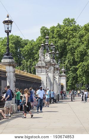 LONDON UNITED KINGDOM- JUNE 21 2017: Tourists in front of the gate to Buckingham Palace. Palace is the London residence and administrative headquarters of the reigning monarch of the United Kingdom