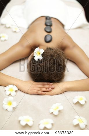 African-American woman with stones on back in spa salon
