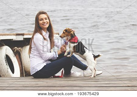 Hey play with me. Horizontal shot of young attractive woman in casual wear playing with her dog and smiling while sitting on wooden pier.