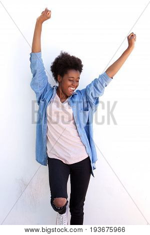 Excited Young African Woman Standing With Her Arms Raised Against White Wall