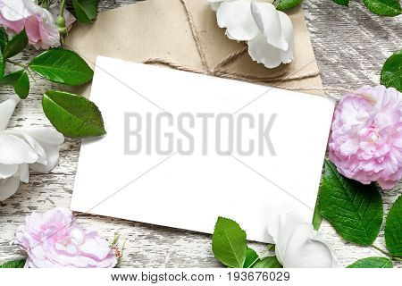 blank white greeting card and envelope in frame of roses flowers over white wooden background. mock up. top view. wedding invitation
