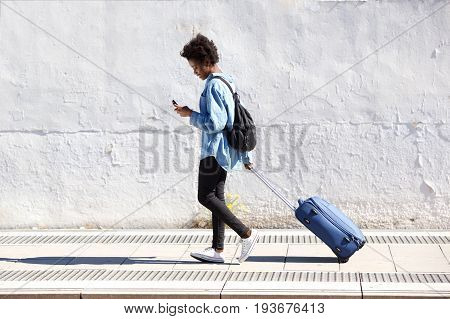African Woman Walking On Railway Platform With Suitcase And Using Mobile Phone