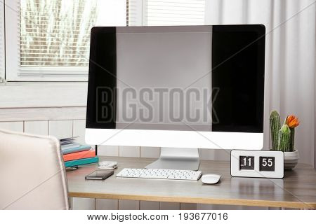 Comfortable workplace with modern monitor and blinds on window