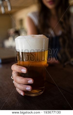 Close-up of barmaid holding beer glass at counter in bar