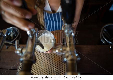 Midsection of barmaid pouring beer from tap in glass at restaurant