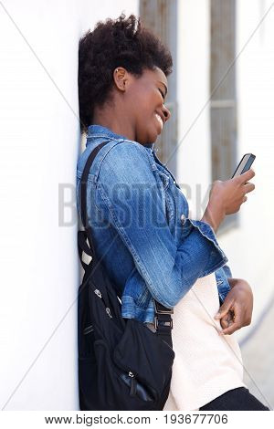 Smiling Young Woman Leaning To Wall And Using Cell Phone