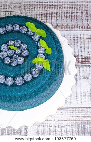 Chocolate velour cake with blueberries and basil leaves