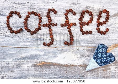 Heart from fabric on table. Coffee beans on wooden background.