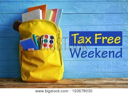 Backpack with school supplies and text TAX FREE WEEKEND on wooden background