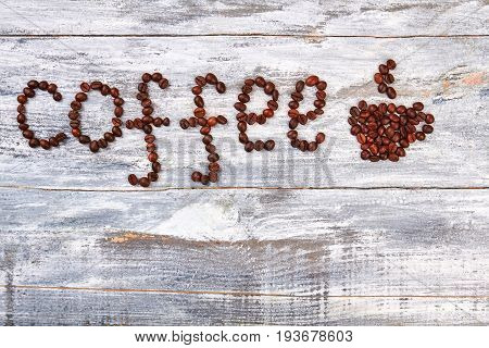 Word coffee from coffee grain. Cup from bean on wooden table.