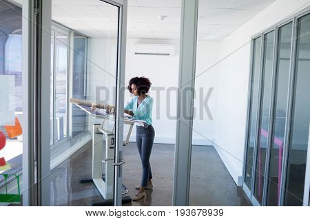 Female architect working on blueprint over drafting table in office