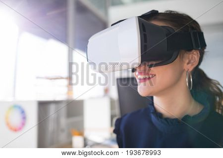 Female architect using virtual reality headset in office