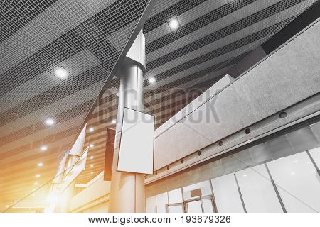 Wide angle view of Information vertical LCD screen or TV in mall interior blank white poster mock-up in hall of airport terminal empty rectangular billboard on the column indoors of modern building