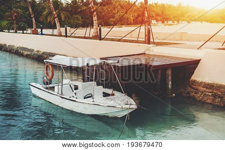 Small old used speedboat with awning parked in teal transparent water to wooden dock near quay wall with stairs with lanterns and palms sand beach with multiple chaise longues in background Maldives