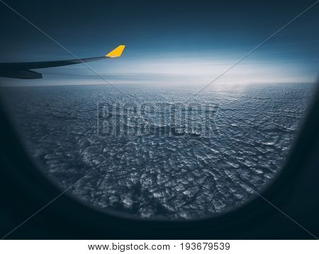 Wide angle shooting through airplane window of aircraft wing with yellow end even maritime cloudscape and dark blue morning horizon cirrostratus clouds in distance