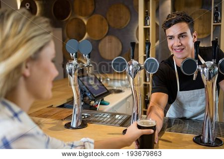 Smiling bartender serving drink to young woman at restaurant