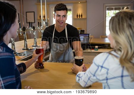 Bartender serving drinks to young female friends at bar counter