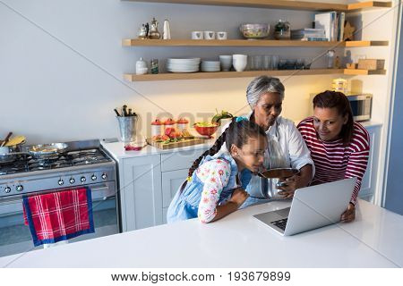 Happy family using laptop in kitchen worktop at home