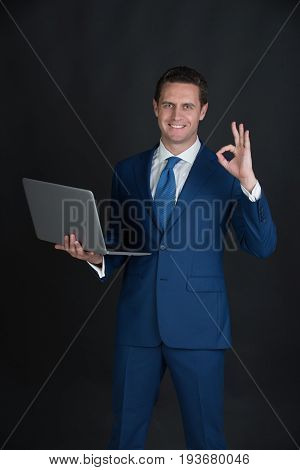 Man working on laptop and making ok gesture on black background. Happy businessman or manager smiling in blue formal suit. Technology for business. Fashion and dress code. Blogging and weblog