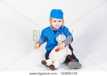 Child In Doctor Uniform Playing Vet With Toy Animal