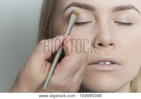 Girl getting eyeshadow powder on eyelids with brush. Eye makeup for pretty woman with young healthy face skin on grey background. Visage skincare cosmetics make up