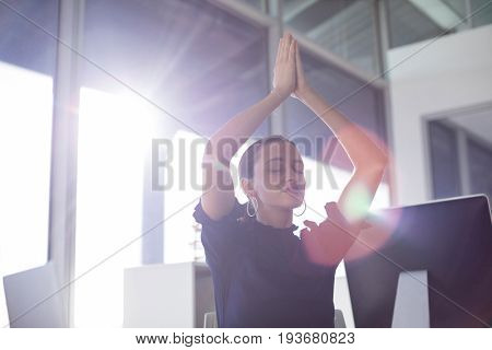 Female executive doing yoga in office