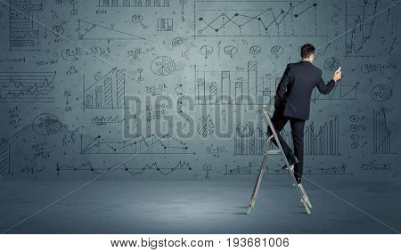 A businessman in modern stylish elegant suit standing on a small ladder and drawing pie and block charts on grey wall background with exponential progressing curves, lines, circles, angles,  numbers