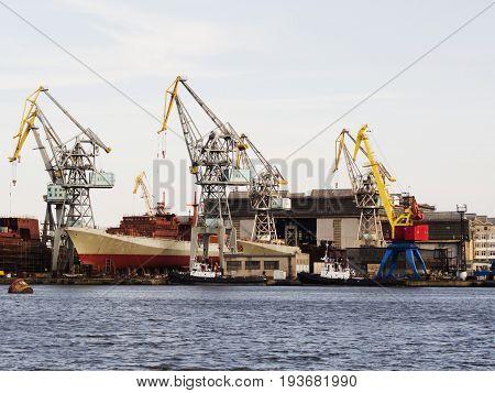 Big ship under repairing on floating dry dock in shipyard.