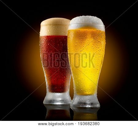 Beer. Cold Craft light and dark Beer in a glass with water drops. Two Craft Beers close up isolated on black background. Pint of beer
