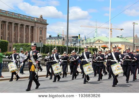 Stockholm, Sweden - June 27 2017: Honorary change of the royal guard. Soldiers and officers in ceremonial uniform with drums march against the background of the Reichstag towards the palace.