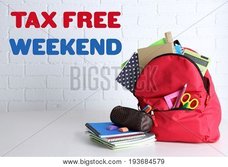 Backpack with school supplies and text TAX FREE WEEKEND on brick wall background