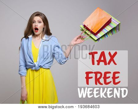 Young woman with paper bags and text TAX FREE WEEKEND on gray background