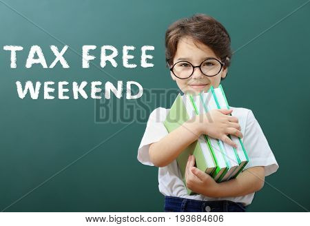 Text TAX FREE WEEKEND, little boy holding books and school blackboard on background
