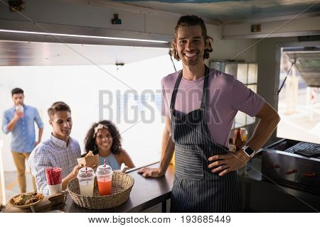 Happy customers and waiter standing at food truck counter