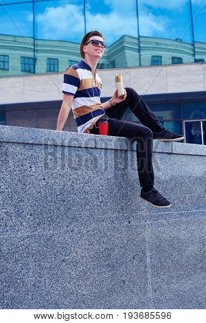 Wide shot of urban boy in jeans and t-shirt enjoying city while having lunch outdoors.