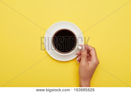 Flat lay of girl hand holding cup of tasty espresso with copy space on yellow background