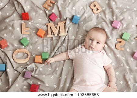 Cute baby with different letters and cubes lying on bed. Choosing name concept