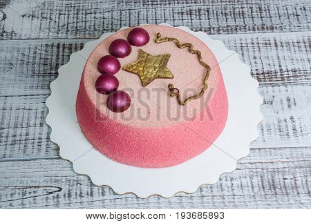 Chocolate velour cake decorated with hemispheres and golden star