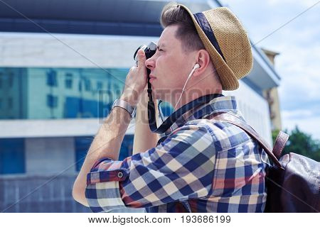 Side view of young man with camera photographing outdoors. Listening to music