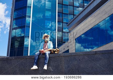 Wide shot of stylish old man enjoying city while drinking coffee and sitting under skyscraper with copy space