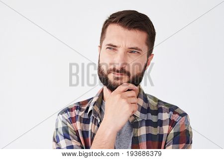 Close-up shot of young thoughtful man with beard holding hand on chin looking side thinking about something important. Isolated over white background