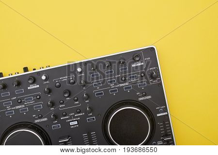 Flat lay of part of  mixing board on yellow background. Musical device lying catty-corner, close-up shot