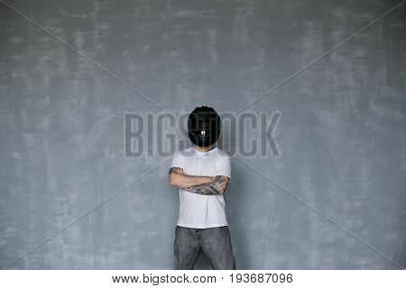 People extreme sports and transportation. Confident young male motorcyclist with tattoos keeping arms folded standing against blank studio wall background with copy space for advertising information