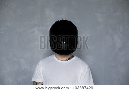 Unrecognizable extreme rider wearing stylish black motorcycle helmet and white t-shirt standing at grey wall in studio. Portrait of European motorcyclist posing indoors with equipment ready for ride