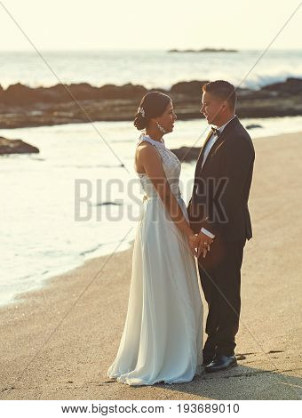 Just married couple on ocean beach sunset light time. Happy groom and bride outdoor