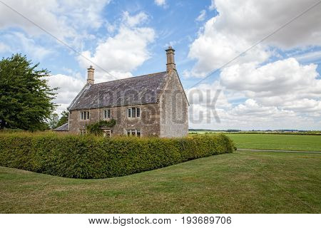 Typical English country cottage. Rural countryside farmhouse.