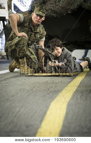 Ship Tour USS Kearsarge (LHD 3) Wasp-class amphibious assault ship: US Navy personnel helps an unidentified boy take aim through the rifle scope of SASR sniper rifle. Fleet Week NEW YORK MAY 25 2017.